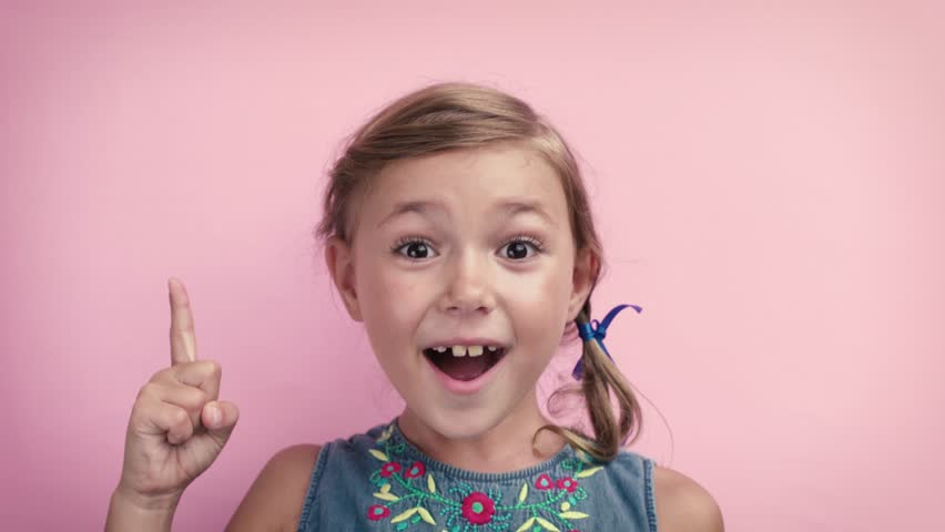 Portrait happy smiling cute girl pointing finger in eureka sign, having great innovative idea on pink background 4K | Shutterstock HD Video #1029229532