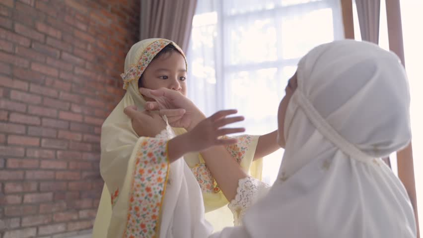 Muslim mother help her young daughter to put head scarf on before pray | Shutterstock HD Video #1029243470