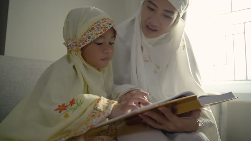 Muslim parent and daughter reading quran after praying together | Shutterstock HD Video #1029261971