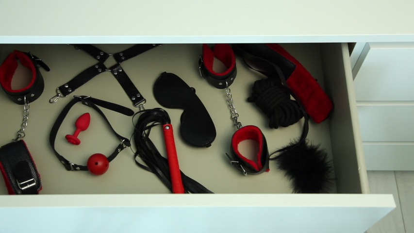 Chest with gag, handcuffs, bandage and whip. BDSM sex toys, erotic entertainment for adults