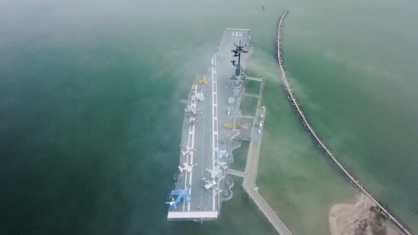Drone flying over aircraft carrier in Corpus Christi looking down on the flight deck in the fog that passes over the navy ship stuck on a sandbar in the gulf.