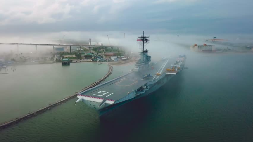 Drone flying around aircraft carrier in Corpus Christi looking at the front of the flight deck in the fog that passes over the navy ship stuck on a sandbar in the gulf.
