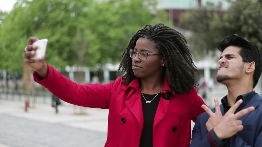 Attractive Afro-american woman in spectacles and rose coat and handsome mixed-race man in navy blue suite making selfie outside, posing, man making faces, girl becoming unsatisfied. Lifestyle concept  | Shutterstock HD Video #1029318809