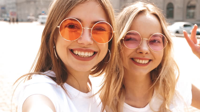 Two young smiling hipster blond women in summer white t-shirt clothes. Girls taking selfie self portrait photos on smartphone.Models posing on street background.Female showing positive face emotions | Shutterstock HD Video #1029329555