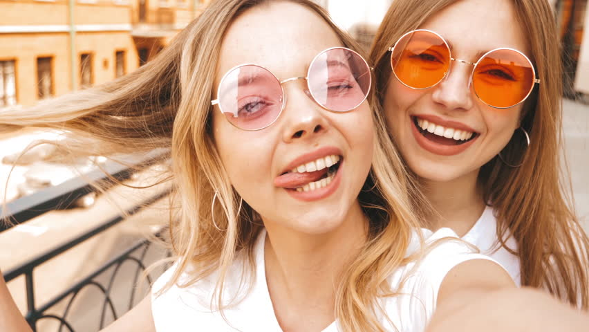 Two young smiling hipster blond women in summer white t-shirt clothes. Girls taking selfie self portrait photos on smartphone.Models posing on street background.Female showing positive face emotions | Shutterstock HD Video #1029329561