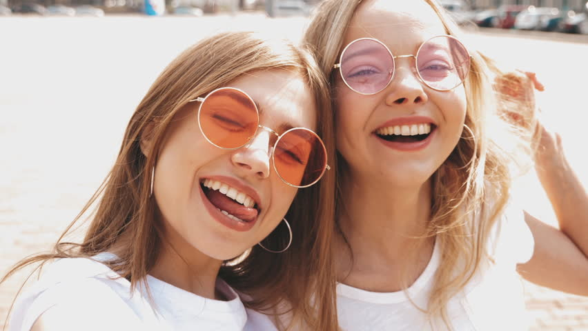 Two young smiling hipster blond women in summer white t-shirt clothes. Girls taking selfie self portrait photos on smartphone.Models posing on street background.Female showing positive face emotions | Shutterstock HD Video #1029329567