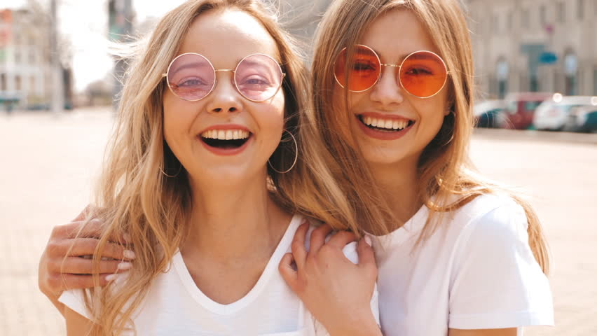 Portrait of two young beautiful blond smiling hipster girls in trendy summer white t-shirt clothes. Sexy carefree women posing on street background. Positive models having fun in sunglasses | Shutterstock HD Video #1029330059