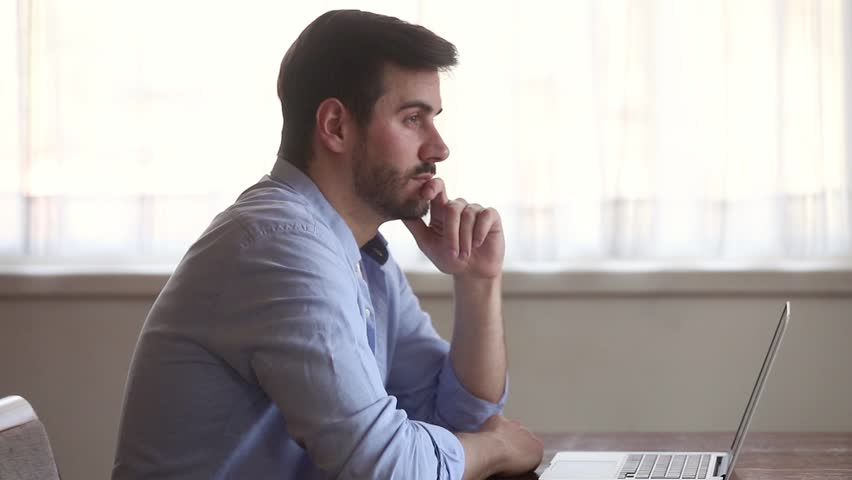 Thoughtful businessman holding hand on chin lost in thoughts at work with laptop, serious pensive man looking away think of problem solution search for inspiration new ideas sit at home office desk | Shutterstock HD Video #1029331775