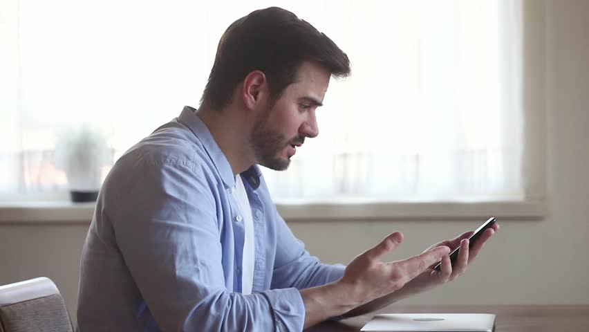 Angry annoyed young business man holding using texting on smartphone frustrated by stuck broken phone missed call bad service, stressed mad male customer outraged having problem complain on cellphone | Shutterstock HD Video #1029331778