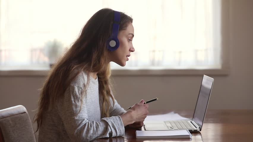 Serious girl student wear headphone study online with internet teacher learn language talk looking at laptop, focused young woman make video call tutoring write notes, teaching concept | Shutterstock HD Video #1029331781