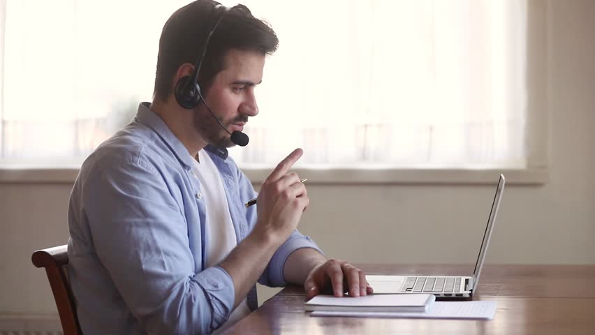 Focused business man interpreter teacher wearing headset looking at laptop screen making notes, male online tutor teaching student learning in internet video calling on computer writing down Royalty-Free Stock Footage #1029331784