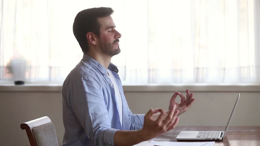 Calm mindful young man taking break sit at home office desk meditating doing exercise feel no stress free relief relaxing, healthy serene guy practicing yoga breathing for peaceful mind and zen | Shutterstock HD Video #1029331787