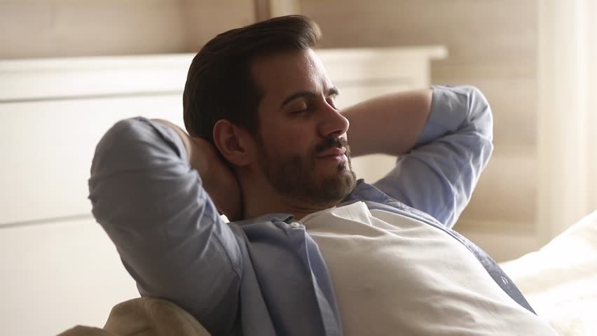 Happy lazy young man relax daydream meditate sit on comfortable sofa at home in living room, calm guy rest breathing fresh air having nap with eyes closed feel peace of mind, no stress free relief | Shutterstock HD Video #1029331793