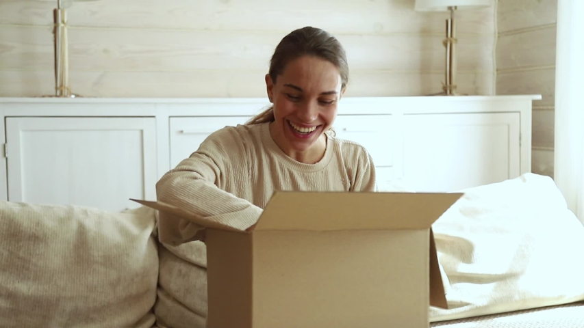 Excited young woman consumer open cardboard box get postal parcel, happy female customer receive carton package with gift sit on sofa at home satisfied with fast shipment online purchase delivery #1029331811