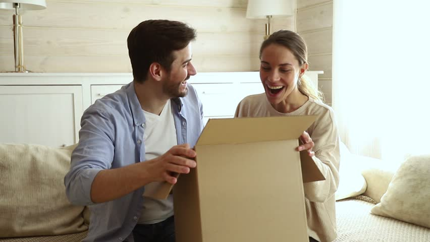 Happy excited couple customers open cardboard box together sit on sofa at home, young family consumers unpack good parcel looking inside receive surprising great purchase delivered by postal shipping #1029331829
