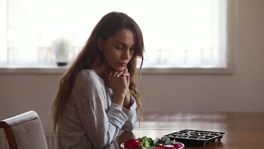 Doubtful unhappy young woman choose between salad and candies at home, upset girl sitting in front of unhealthy chocolate sweets vegetable on table, healthy vs unhealthy food difficult choice concept #1029331844