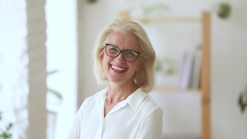 Head shot of fifty years woman wearing glasses pose in office room looking at camera laughing feels happy, independent elderly company owner, coach or leader successful businesswoman portrait concept Royalty-Free Stock Footage #1029333209