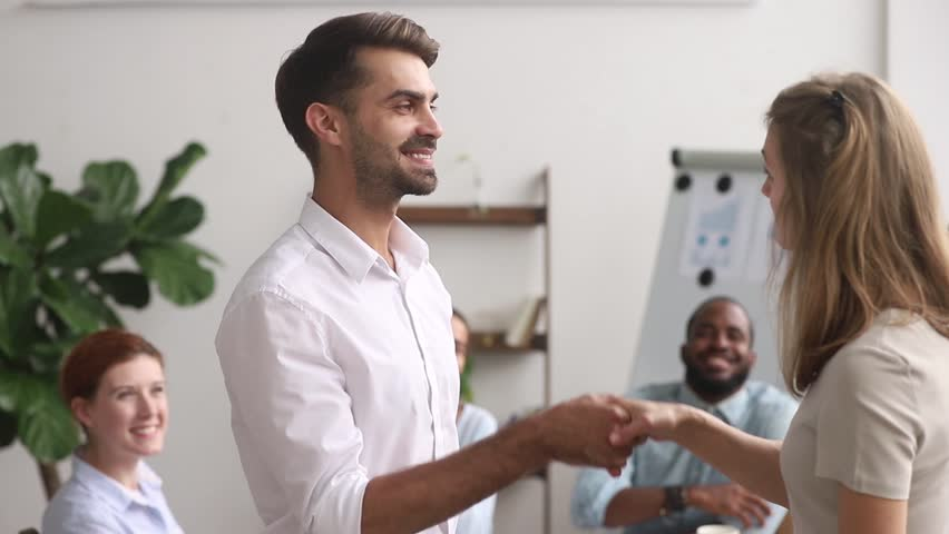 Multi-ethnic employees clap hands while boss greeting corporate client, happy businesswoman ceo congratulate shake hands successful worker getting reward or promotion, handshake as symbol of gratitude Royalty-Free Stock Footage #1029333284
