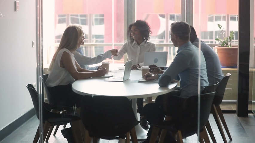 Multi-ethnic business partners gathered negotiate in boardroom behind closed doors view through glass, entities parties after discuss details of agreement signing contract shake hands feels satisfied Royalty-Free Stock Footage #1029333314