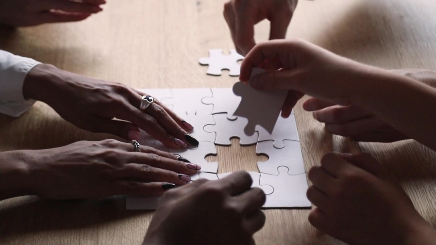 Side view hands of united diverse people taking part assembling white jigsaw puzzle, different ethnicity friends put pieces together search common solution, help support teamwork and synergy concept #1029333320
