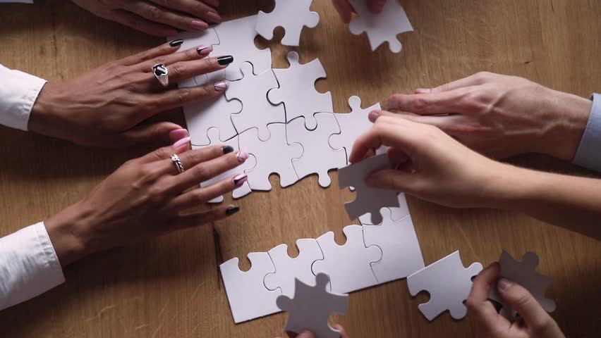 Above close up view hands multi-ethnic business people teammates connects together white pieces of jigsaw puzzle on office desk, participating team building activity, search solutions, synergy concept Royalty-Free Stock Footage #1029333326