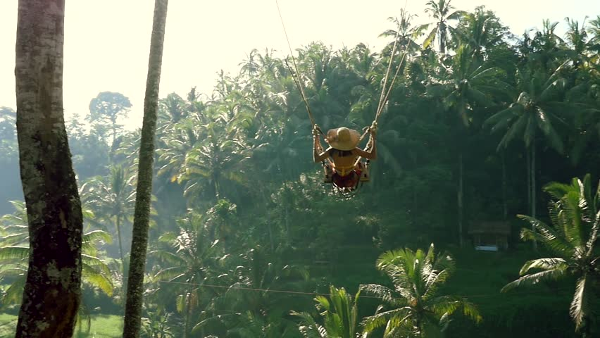 Beautiful girl swinging over the jungle in Bali Royalty-Free Stock Footage #1029337757