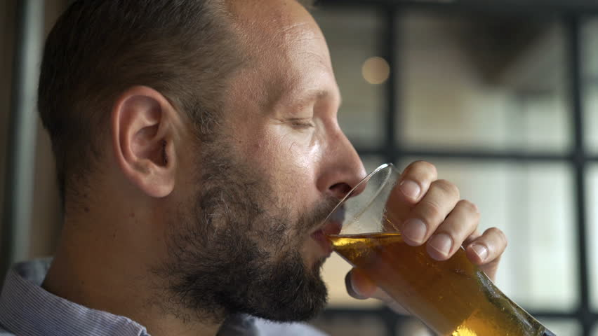 Young man drinking beer in cafe | Shutterstock HD Video #1029350390