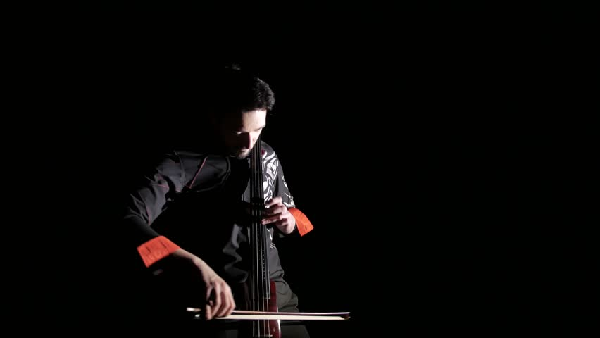 young handsome man plays electric cello on black background, isolated