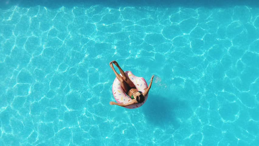 Girl in the pool swims on an inflatable donut of pink color