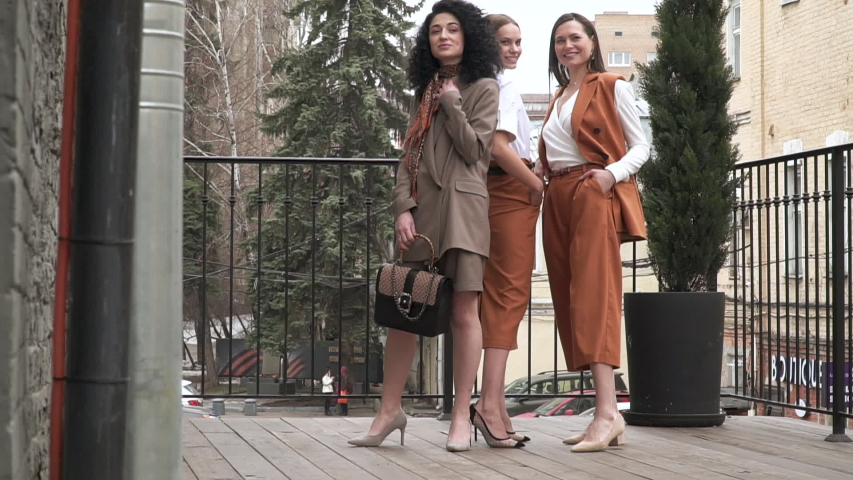 HD Footage. Slowmo. Three beautiful young girls in business suits. Business style. Posing at a photo shoot in the studio.   Shutterstock HD Video #1029365408