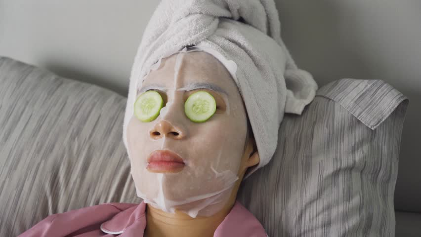 Young woman wearing facial mask with cucumber slices covering her eyes and relaxing on the bed with a towel on head. Shot in 4k resolution   Shutterstock HD Video #1029367055