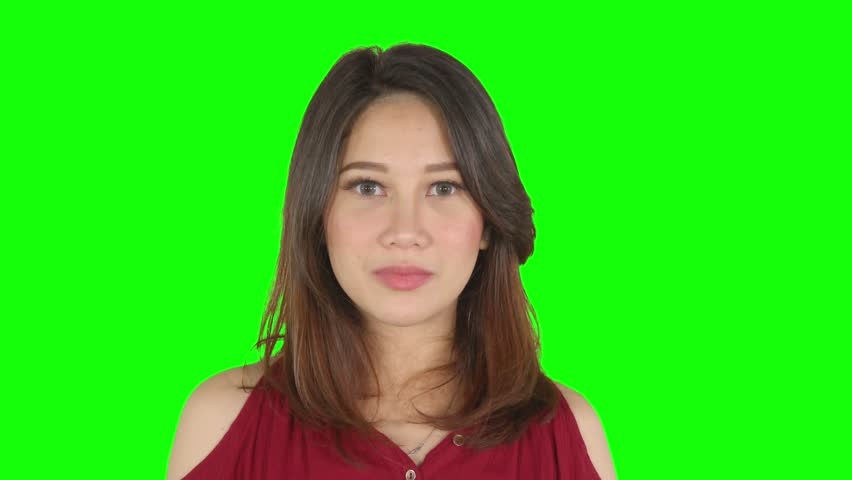 Beautiful young woman looks surprised staring at the camera and smiling happy. Shot in 4k resolution with green screen background | Shutterstock HD Video #1029367073