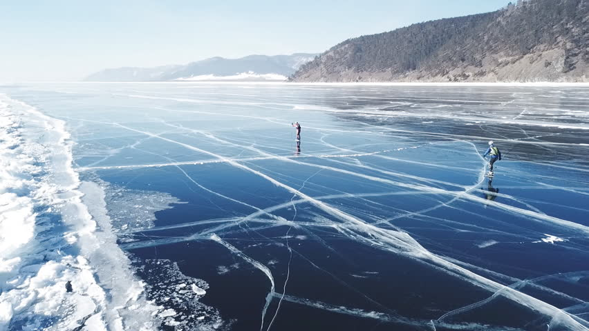 People tourist walk go on smooth surface. Picturesque Lake Baikal Cracks blue glossy clear ice hummocks snow snowdrifts. Best North Russia Asia. Winter sunny day blue sky. Aerial Approach.