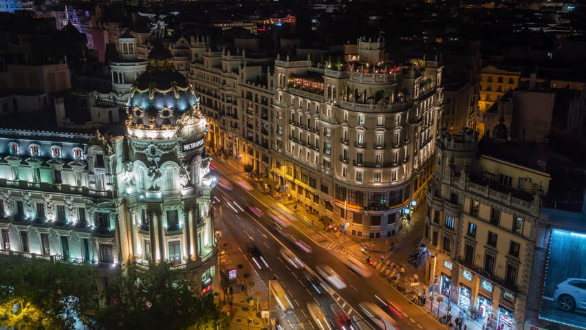 Night time lapse view of architectural landmark Metropolis building and traffic on Gran Via street in central Madrid, Spain. Royalty-Free Stock Footage #1029384632