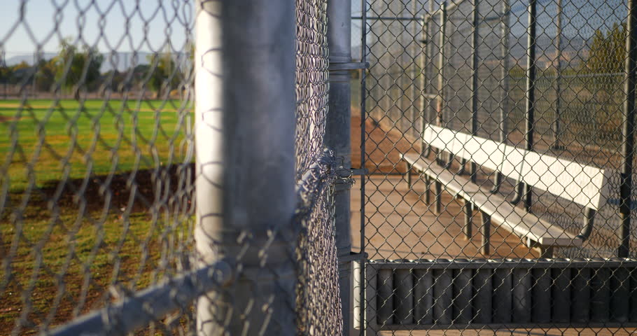 Slow pan across a chain link fence and an empty baseball field bench in the dugout of a local park at sunrise.