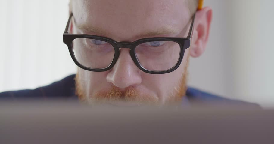 Close up face of young bearded caucasian entrepreneur in glasses looks attentively at computer screen | Shutterstock HD Video #1029403466