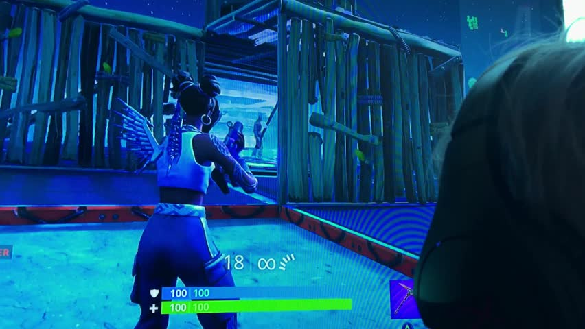 Fortnite Video Game Playing Closeup Footage. Young boy playing popular game with big tv screen. 7th April 2019. Finland, Espoo.
