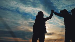 teamwork hands. business journey concept win. happy family team tourists man and woman sunset silhouette help shake teamwork hands victory success lifestyle . slow motion video. tourism husband top