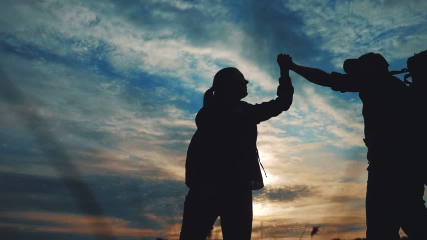 Teamwork business journey concept win. happy family team tourists man and woman sunset silhouette help shake hands victory success lifestyle . slow motion video. tourism husband and wife on top of the | Shutterstock HD Video #1029417956