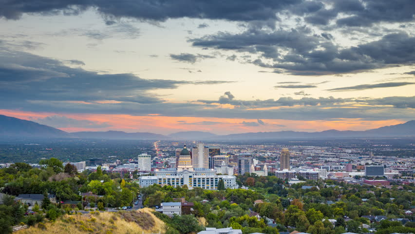 Day to night time-lapse video of Salt Lake City skyline panorama with famous Utah State Capitol on a beautiful summer day with dramatic moving cloudscape and slight zoom out effect, Utah, western USA