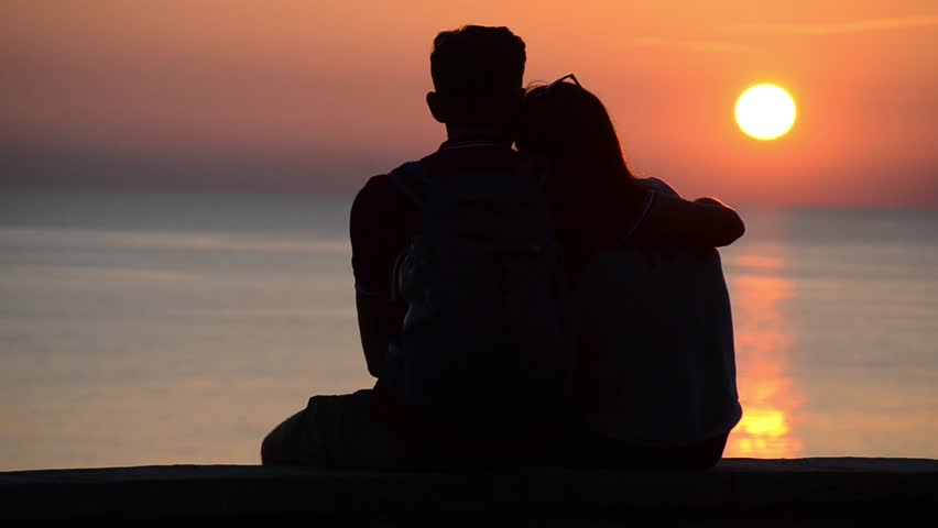Silhouette of couple in love at sea in golden and beautiful sunset. Young and romantic couple enjoying.  Boy and girl on holidays on romantic summer evening. Happy couple talking and hugging on beach