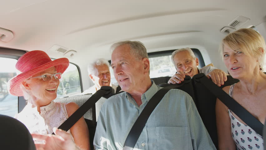 Group Of Senior Friends Sitting In Back Of People Carrier Being Driven To Vacation