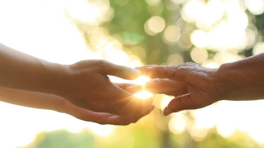 Hand of young man holds the hand of an elderly person with love and warm feeling, metaphor Help for the eldery, nursing home, Help to relatives, warm family