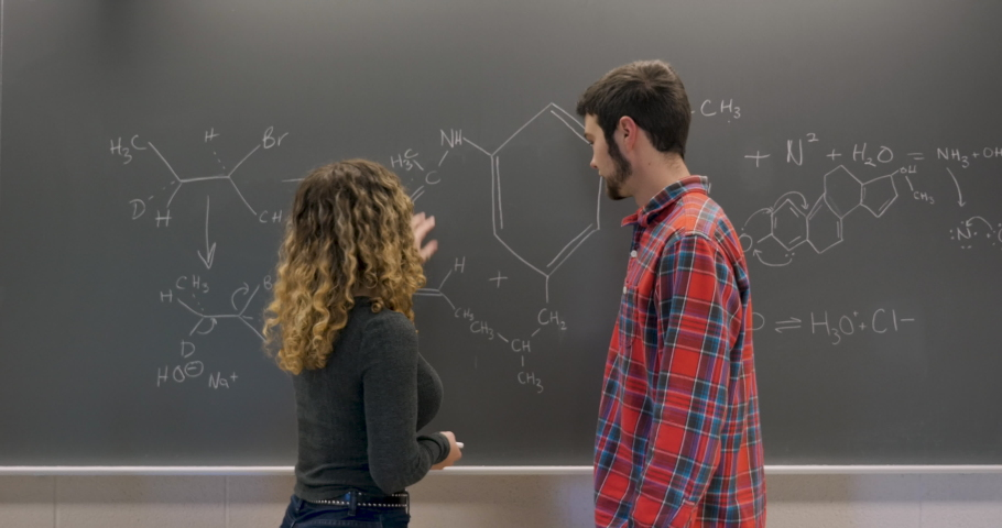 Young female college student explaining a hard chemical formula to a male student using chalk on a blackboard Royalty-Free Stock Footage #1029494294
