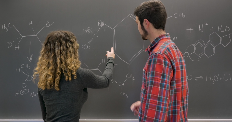 Male and female students working together collaborating and solving complex problems on a chalkboard Royalty-Free Stock Footage #1029494306