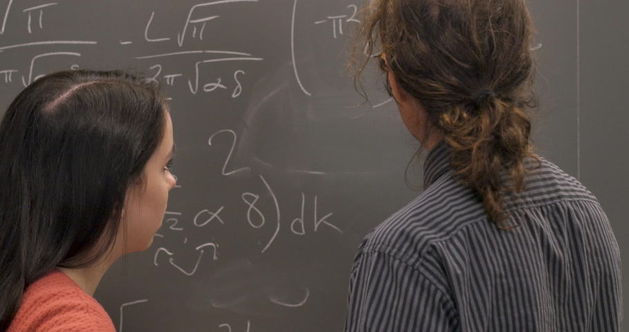 Two scientists or mathematicians agreeing on a solution to a complex problem written on a blackboard Royalty-Free Stock Footage #1029494714