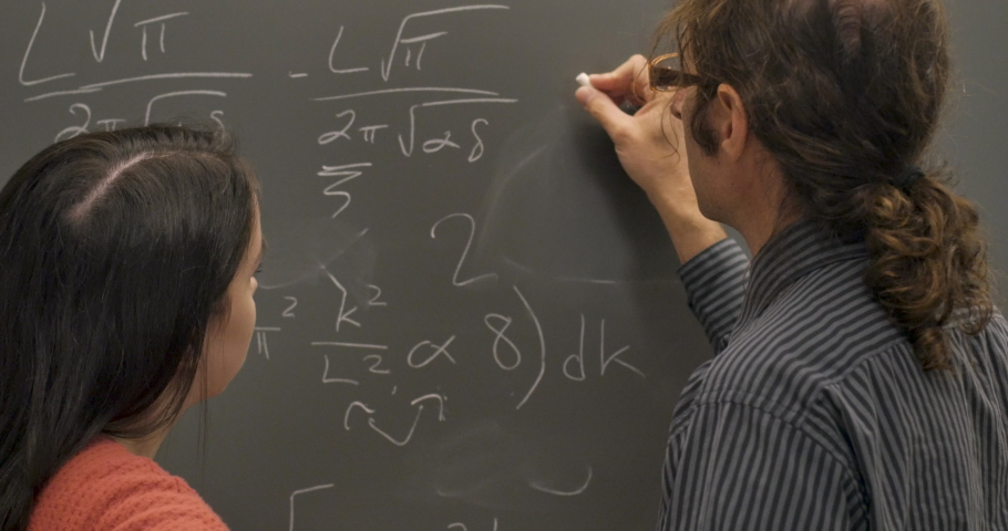 Man and young woman working and collaborating together on a complicate problem on a chalkboard Royalty-Free Stock Footage #1029494723