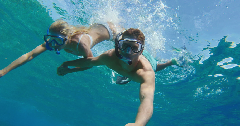 POV shot of young attractive couple diving down and snorkeling together in tropical ocean water, summer vacation fun
