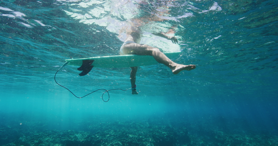 Underwater angle of female surfer sitting on her surfboard waiting for a wave in the ocean #1029503753