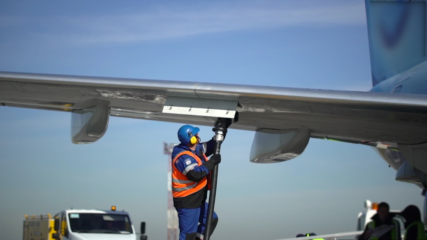 Airport airplane crew refueling aircraft on airline by technical staff maintenance ground. Preparing airplane for departure. service worker using fuel hose on aircraft wing, jet aviation fuel kerosene
